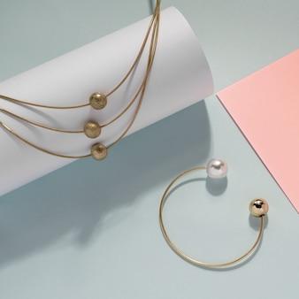 黄金のネックレスとパステルカラーの背景にパールのブレスレット