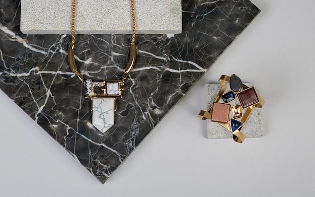 Golden necklace and bracelet on dark granite natural rock