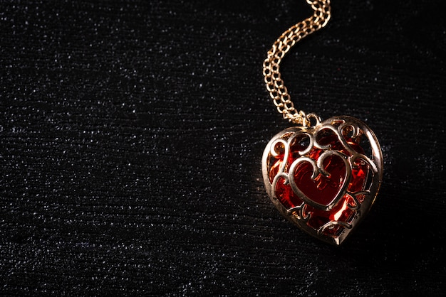 Golden necklace with diamond red heart on black background