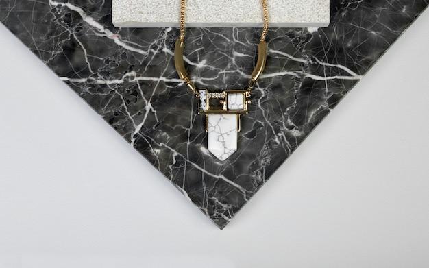 Golden necklace with gem stone on dark granite natural rock