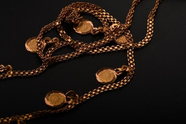 黒い表面に隔離された金色のネックレス