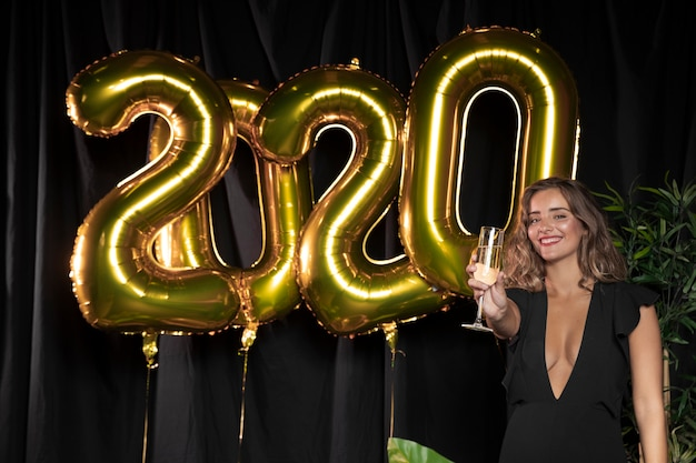 Golden new year 2020 balloons and cute girl holding a glass of champagne