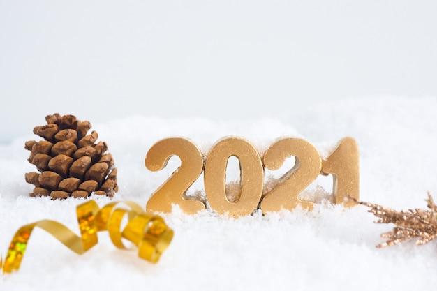 Золотые числа 2021, еловая шишка и серпантин на снегу.