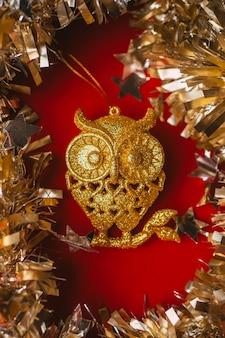 赤い背景の上の黄金のフクロウのクリスマスツリーのおもちゃ