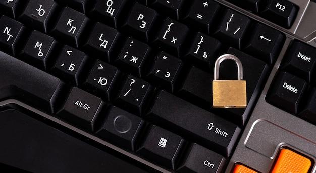 Golden padlock on laptop keyboard, information security protection, password
