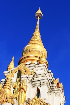 Golden pagoda in temple located on the mountain and beautiful blue sky