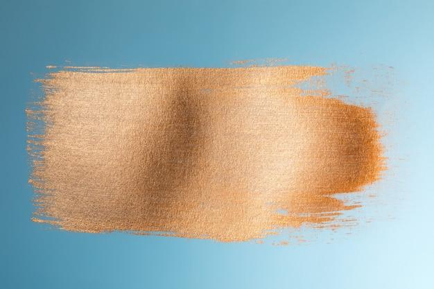 Golden paint brush stroke on blue paper