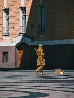 街の通りに描かれた黄金色の芸術家、生きた銅像は通行人の娯楽です。セントピーターズバーグ。着色画像。