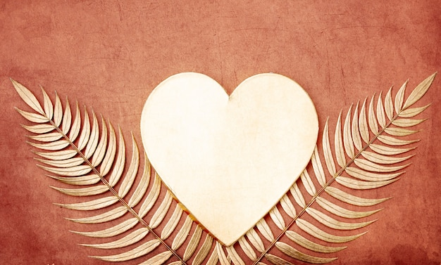 Golden palm branches and heart shape on pink.