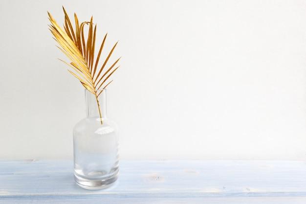 Golden palm leaf in glass vase bottle on light background.