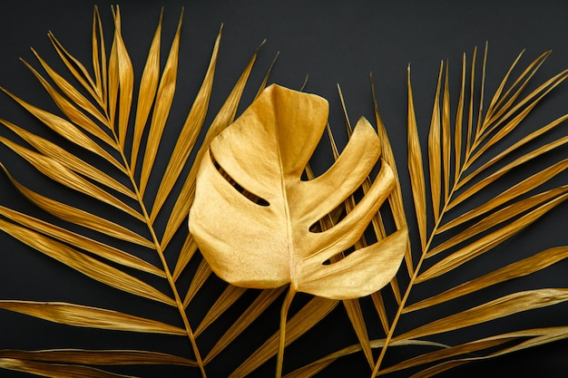 Golden palm leaf, tropical monstera leave texture on dark black background. painted gold leaves of tropical plants on summer floral background.