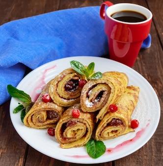 나무 테이블에 흰 접시에 딸기 잼과 가루 설탕 롤의 형태로 골든 팬케이크. 확대. 아침밥