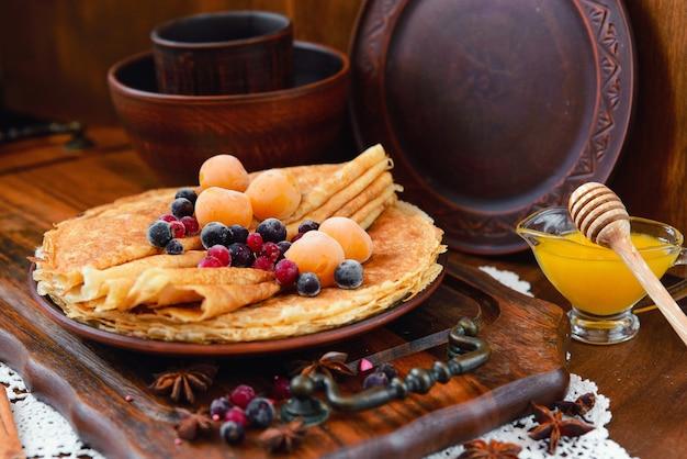 Золотые блины с замороженными фруктами, декором и медом в деревенском стиле
