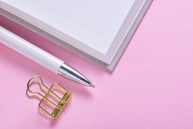 Золотая скрепка и карандаш на блокноте-календаре-органайзере