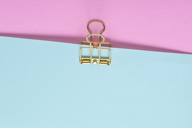 Golden paper clip and  paper sheets on blue and pink background