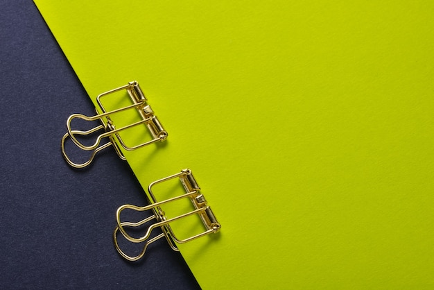 Golden paper clip and  paper sheets on green and black background