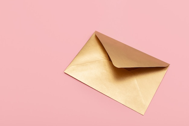 Золотой бумажный конверт, изолированные на розовом