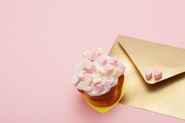 마시멜로와 발렌타인 컵케익 핑크에 고립 된 두 마음으로 황금 종이 봉투