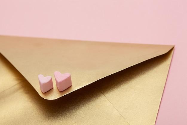 마쉬 멜 로우 분홍색 배경에 고립에서 두 마음으로 황금 종이 봉투