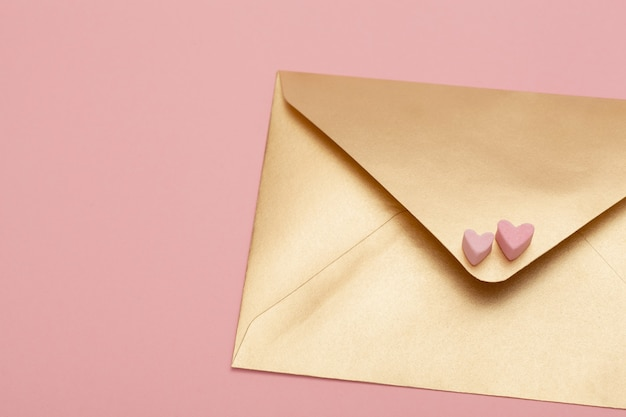 Golden paper envelope with two hearts from marshmallow isolated on pink background