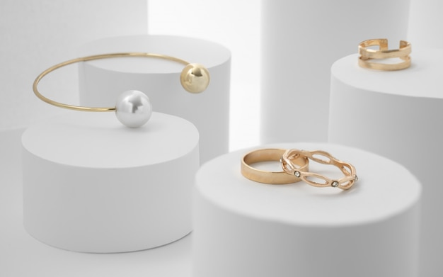 Golden pearl bracelet and rings on white paper cylinders