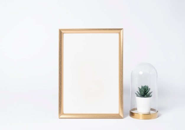 Golden photo frame mock up and plants in vase interior decor home elements.