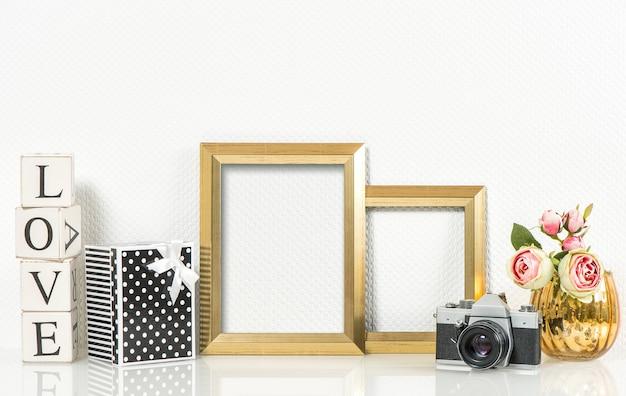 황금 액자, 장미 꽃, 이름 없는 빈티지 사진 카메라. 레트로 스타일 장식