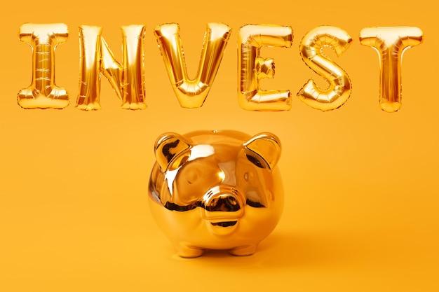 Золотая копилка на желтом фоне с золотым словом invest из надувных воздушных шаров из фольги. инвестиционная и банковская концепция. экономия денег, копилка, финансы, инвестиции.