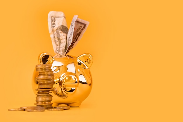 Golden piggy bank with money tower and euro bills on yellow background