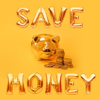 Golden piggy bank with money towers and balloon words save money on yellow background. money pig, money saving, moneybox, finance and investments concept.