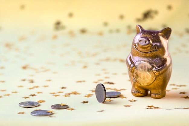 가벼운 벽에 흩어져 돈 동전과 황금 돼지 저금통