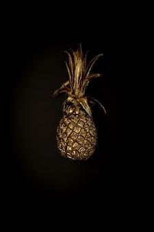 Золотой ананас на черном фоне, стильная минималистичная композиция с copyspace для рекламы. модное ультрамодное сочетание цветов. еда, фрукты, сладости, концепция летних флюидов. постер, обои.