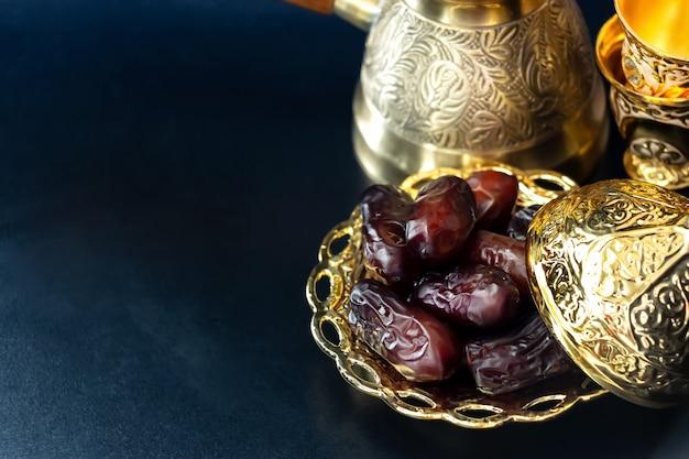 乾燥ナツメヤシの実やクルマの黄金のプレート。ラマダンカリームのコンセプトです。閉じる。