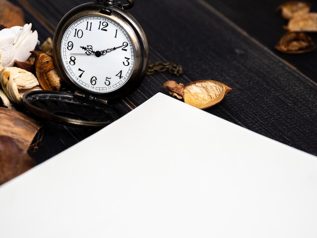 Golden pocket watch put on dried leaves and blank notebook on wooden retro black table.