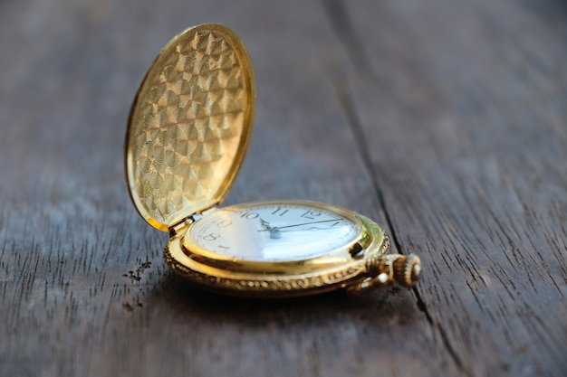 Golden  pocketwatch classic design watch 10.10 hour put on wood table background