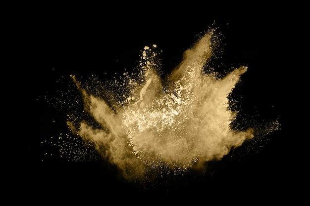 Golden powder explosion on black background.