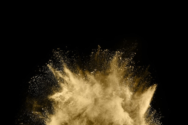 Golden powder explosion on black background