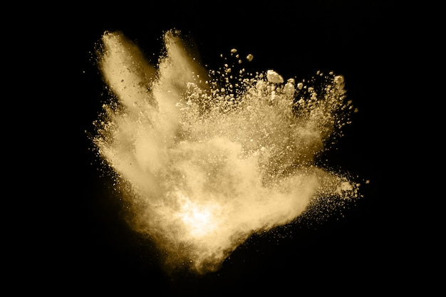 Golden powder explosion on black background.