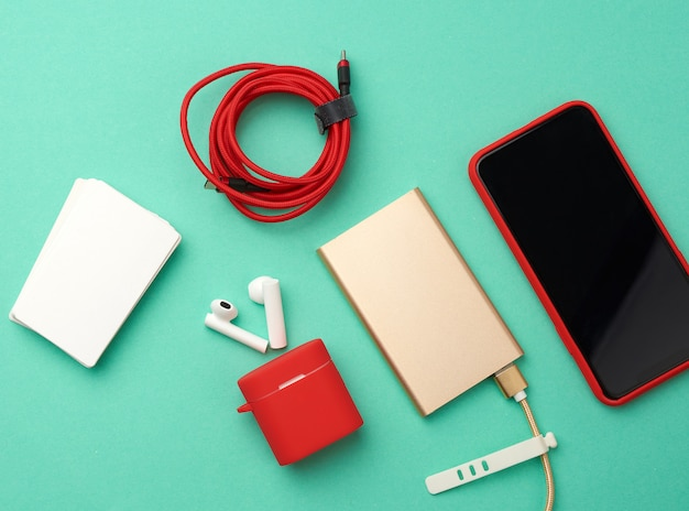 Golden power bank with cable, red smartphone with blank black screen, box with headphones, empty paper business business cards