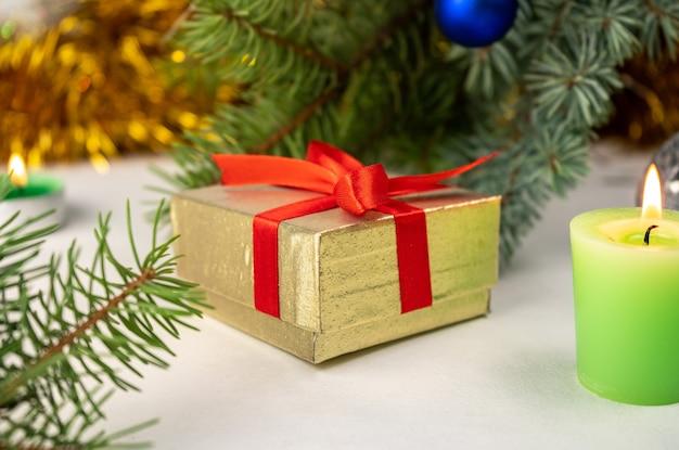 크리스마스 트리, 양 초 및 휴일 장식 옆에 빨간 리본이 달린 황금 선물 선물 상자. 메리 크리스마스 또는 새 해 복 많이 인사말 카드. 흰 배경