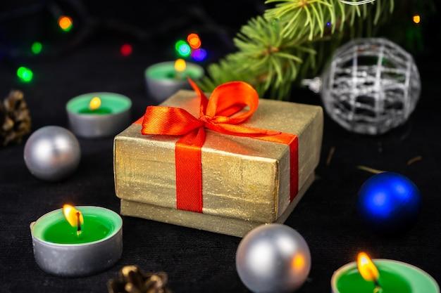 Золотая подарочная коробка с красной лентой рядом с елкой, свечами и праздничным украшением.
