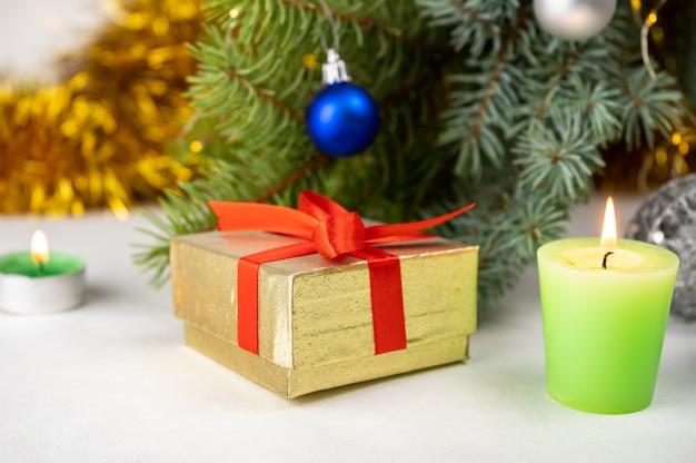 크리스마스 트리, 양 초 및 휴일 장식 옆에 빨간 리본이 달린 황금 선물 선물 상자.