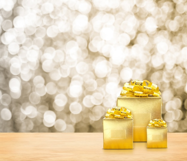 Golden presents on wood table top with gold sparkling bokeh light.