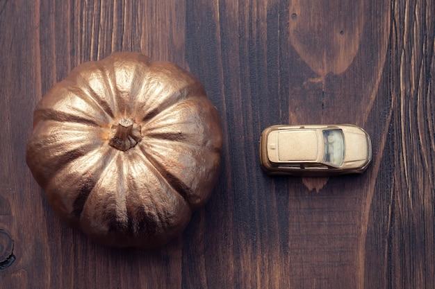 Золотая тыква и золотой маленький автомобиль на коричневом деревянном фоне