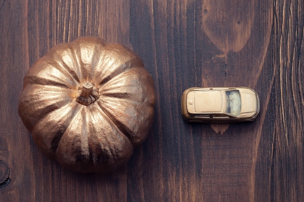 Golden pumpkin and golden small car on brown wooden background