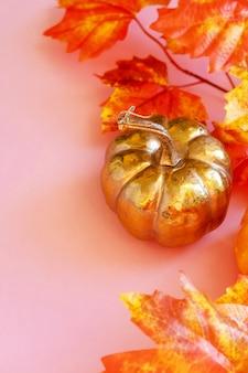 ピンクのカエデの葉と黄金のカボチャ