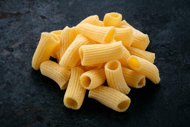 어두운 돌 배경에 황금 생 리가토니 달걀 파스타. 이탈리아 파스타의 종류, 클로즈업