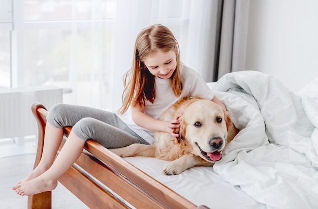 골든 리트리버 강아지 침대에서 쉬고 어린 소녀가 그를 쓰다듬는 동안 카메라를 찾고. 아침에 애완 동물 강아지와 함께 집에 머무는 아이. 주인이있는 가축