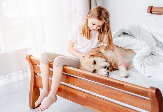 어린 소녀가 그를 쓰다듬는 동안 골든 리트리버 강아지는 침대에서 쉬고 있습니다. 아침에 애완견과 함께 집에 있는 아이. 주인이 있는 가축