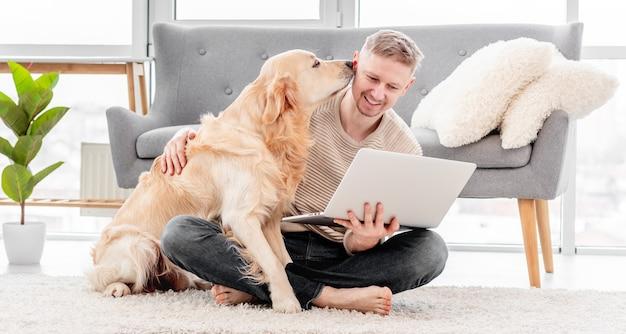 골든 리트리버 개는 노트북을 들고 남자 소유자를 막습니다
